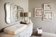 Reclaimed dresser serves as both storage and a changing table, while the mirror repeats the soft color of the curtains and framed prints above the crib.