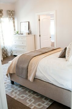 light walls, white bedding, seating at foot, gray blanket, upholstered headboard, patterned throw pillows, brown patterned curtains, LOVE the rug!