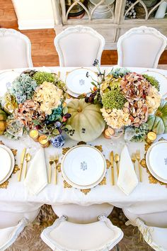 Elegant Heirloom Thanksgiving Table Scape with blue, purple and white hydrangeas, blue ginger jars, and green heirloom pumpkins. Monogram plates and gold flatware, stemware, chargers, and votives.