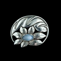 Early 20th century flower-motif brooch by Georg Jensen. This very collectible, asymmetrical sterling pin features a lovely oval cabochon moonstone. A beautiful Jensen piece. Signed Georg Jensen U.S.A. #175.