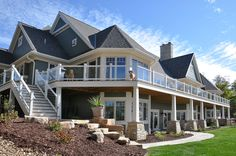 Glass paneled upper deck railings add a modern twist to this traditional home exterior by Van's Lumber. #DreamHome