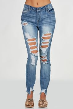 Mid rise skinny jeans with heavy distressing in front. Medium wash with trendy frayed raw hem finish.