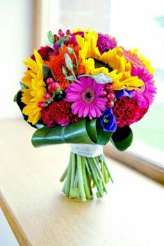 Bright Candy Colored Wedding Bouquet With: Yellow Sunflowers, Fuchsia Gerbera Daisies, Orange Gerbera Daisies, Fuchsia Coxcomb, Red Coxcomb, Blue-Violet Florals, Hypericum Berries & Emerald Green Aspidistra