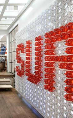 Plastic Drink Bottles Were Reused To Create A Giant Logo For This Office. The large red and white logo is made from over 900 bottles that are backlit, making it appear more like a piece of contemporary artwork than a typical company logo. Wayfinding Signage, Signage Design, Booth Design, Wall Design, Environmental Graphic Design, Environmental Graphics, Plastic Drink Bottles, Trash Art, Retail Design