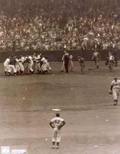 "Jackie Robinson, Brooklyn Dodgers, watches as New York Giants players celebrate Bobby Thomson's ""shot heard 'round the world."" Losing pitcher Ralph Branca heads toward clubhouse."