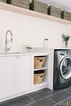 Laundry room remodel with open shelving, built in laundry baskets, wallpaper, and a folding counter. #laundry #laundryroom #interiordesignideas