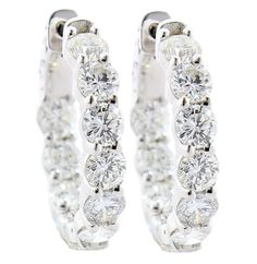 These incredible inside out hoop earrings feature 4.29 carats of brilliant cut diamonds set in 14 karat white gold.