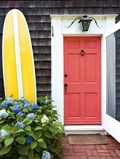 coral door, weathered shingles, hydrangeas and a yellow surf board