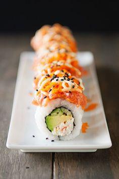 Sushi Roll: Krabbenfleisch, Avocado, Gurke getoppt mit gewürzten Thunfisch, Masago, Sriracha Mayo und Wasabi Mayo