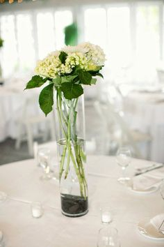 My fiance and I both love doing exactly this idea: these white hydrangeas in a tall cylindrical vase with the river stones at the bottom for each table. Simple but beautiful. And affordable!