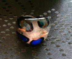 Imposanter Ring aus Glas. Untergrund ist eine Silberfolie mit Kupfersprengseln. Blaue und türkisfarbene, metallschimmernde Flecken, eingerahmt in schwarz. Innenreif ist undurchsichtig schwarz. Auf...