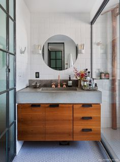 Espelho redondo, bancada de concreto e piso com pastilhas no formato de colméia.