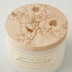 """Skeem Flower Market Candle from Terrain. This soy blend candle is boldly scented with fresh cut jasmine, rose blossoms, and cedar.  Each candle is poured into a glass jar with an etched wooden lid. Triple cotton wick. 80 hour burn time. 3.5""""H x 4.6""""Diameter. $38.00"""