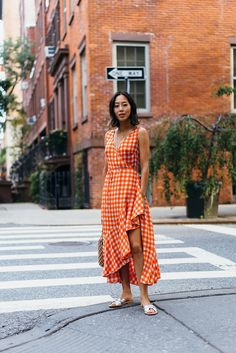 Aimee Song of the blog Song of Style shares an outfit post from New York City, wearing a DVF gingham wrap dress and metallic Loeffler Randall sandals.