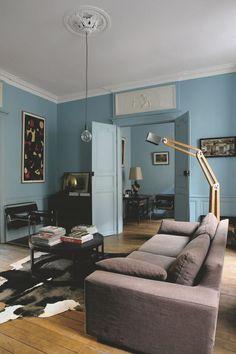 Dans le salon au bleu gustavien et hauts reliefs en plâtre, peinture (Galerie Jean-Marc Lelouch) ; canapé (AMPM) ; fauteuils Wassily, de Marcel Breuer (Knoll) ; lampadaire articulé de François Champsaur.
