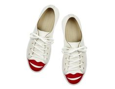 The iconic Charlotte Olympia lips make a witty addition to the toes of these sleek and simple Kiss Me Sneakers. In off white and red leather, this pair brings life to your casual styles.