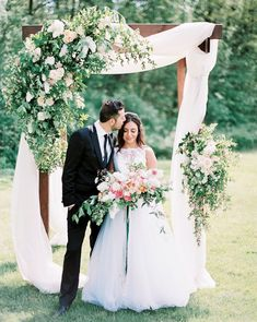 A lush asymmetrical swag of green smilax vines, ivory Vendela roses, dusty blush Quicksand roses, ivory spray roses, and white stock flowers on the left side of the ceremony arch