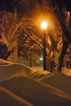 Streetlamp Glowing on Snow Mounds
