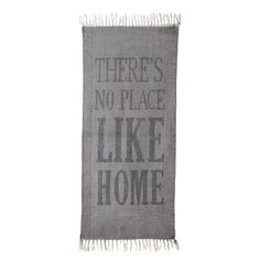"""This contemporary rug from Bloomingville combines subtle style with bold detailing. In a simple grey colour with classic fringed edges, it bears the text """"There's no place like home"""" in large, cont..."""