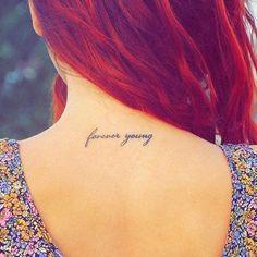 """Pequeño tatuaje en la espalda que dice """"forever young"""", que significa """"joven para siempre""""."""