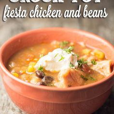 Crock Pot Fiesta Chicken and Beans Recipe Main Dishes with chicken thighs, salt, pepper, onions, garlic, diced tomatoes, black beans, chili beans, frozen corn, salsa, tomato sauce, ground cumin, garlic powder, cilantro, sour cream, guacamole