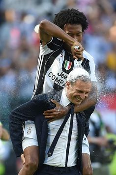"""Juventus' forward from Colombia Juan Cuadrado (top) celebrates with Juventus' coach from Italy Massimiliano Allegri after winning the Italian Serie A football match Juventus vs Crotone and the """"Scudetto"""" at the Juventus Stadium in Turin on May 21, 2017. First-half goals from Mario Mandzukic and Paulo Dybala, and a late header from Alex Sandro sealed a 3-0 win over Crotone to hand Juventus a record sixth consecutive Serie A title today. / AFP PHOTO / Filippo MONTEFORTE"""