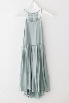 Delicate aqua colored dress with a high neckline and flowy high-low bottom…