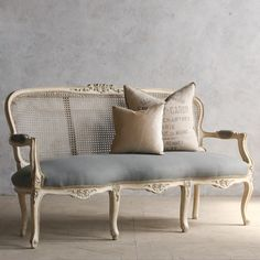 Feminine vintage settee with a weathered antique white finish and light slate blue upholstery. Cane back has some small flaws.BRBR37H x 64W x 27DBRSeat Height: 19BRArm Height: 25BRCirca: 1930BR BR Return Policy:BR This item is not eligible for returns or exchanges so please make sure to look over the pictures and ask questions before purchasing this beautiful piece.BR