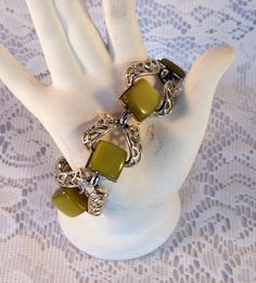 Coro signed moonglow lucite in an interesting olive green color. Lovely silver tone filigree links the lucite pieces together. It measures