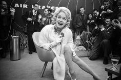 Les plus belles photos des  archives de Paris Match - 1962 - L'actrice allemande Marlène Dietrich qui chante sur les scènes du monde entier depuis 1960 viens d'arriver à Orly. Elle pose dans un salon de l'aéroport  devant une cohorte de journalistes de photographes. Photo : Philippe le Tellier / Paris Match