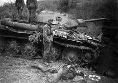 A German Mountain Division trooper contemplates a destroyed Russian T-34 tank and Red Army soldier killed in action.
