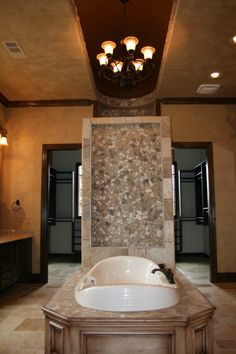 A peninsula jetted master bath tub underneath a domed barrel ceiling in a rustic custom home in Southlake, Texas.  The wall behind the tub has a built in waterfall.     Behind the waterfall wall is a two person tub with body sprays and a rain head.     The doors on either side lead into a massive closet.