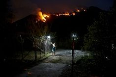 A woman closes a gate on her land as a forest fire rages on a nearby mountain in Cajón del Maipo, on the outskirts of Santiago Photograph: Esteban Felix/AP