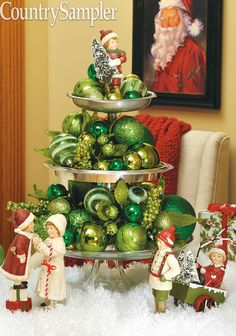 Stack three cake stands or other small serving dishes with pedestals and fill each layer with an assortment of green glass ball ornaments. Add holiday figures to the scene and top of stack, filling in with faux snow.