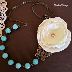 """Beautiful romantic handmade statement choker consists of a handcrafted off white fabric flower w/ a rhinestone button in the center, a filigree lace butterfly pendant, turquoise howlite pearl beads, and an antique gold brass chain. A brass clasp was added at the back for closure.    The flower was made with high quality off white wedding satin and chiffon material    Length: approx. 11"""" long when worn (If you desire more length, no problem, at checkout please state in the """"Note to Seller""""…"""