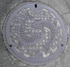 A pair of salmon dance on the Miyako manhole cover design.