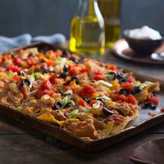 Crispy corn tortilla chips smothered with beans, chicken and cheese and topped with tomatoes, green onions and ripe olives