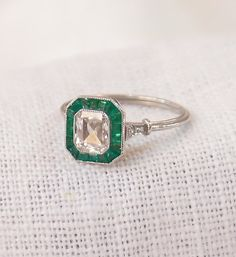 Gorgeous diamond and emerald engagement ring from the Art Deco era. The ring is crafted of platinum, and features a very high quality .85 carat