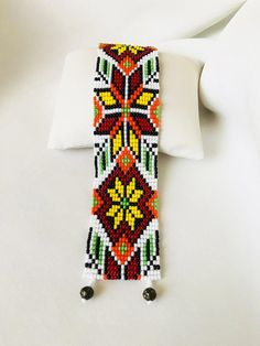 Loom beaded cuff bracelet with Ukrainian ethnic ornament on white background in green, yellow, orange and brown shades. This pattern carries an Ukrainian folk c Loom Bracelet Patterns, Beaded Earrings Patterns, Bead Loom Patterns, Jewelry Patterns, Beading Patterns, Flower Patterns, Beaded Cuff Bracelet, Bead Loom Bracelets, Native American Beadwork