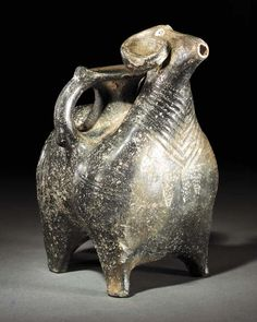 """AN URARTIAN BLACK BURNISHED POTTERY RAM RHYTON  9TH-8TH CENTURY B.C.  The animal standing four-square, with broad cylindrical body on short tapering legs, its head with tapering muzzle, white infilled dotted circular eyes and large inward-curled horns, with grooved neck folds & three white incised dotted triangles on its chest, further grooved decoration on its legs, with broad strap tail decorated with white infilled dots, circular mouth of the vessel emerging from its back...  9"""" high"""