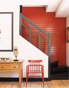 A red wall catches the light in a stairwell and seems to expand the space. Via House Beautiful.