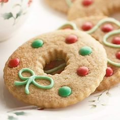 Cinnamon Wreaths  Jazz up simple wreath cookies with creamy white chocolate frosting (see recipe) and red and green chocolate pieces.
