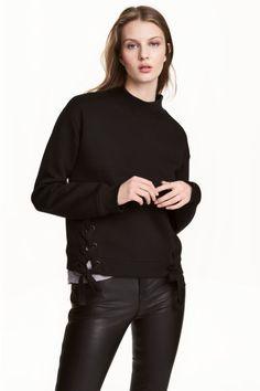 Camisola sweat com atilhos: Camisola de mangas compridas em tecido moletão. Modelo com atilhos cruzados nos lados e remate do decote, punhos e cós em malha canelada. Interior cardado e macio.