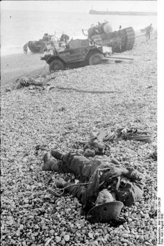 A fallen Canadian soldier with a bullet hole in his helmet lies on the pebble beaches of Dieppe after the failed Dieppe Raid (August 19, 1942)