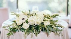 Overflowing cream florals, greenery, seeded eucalyptus on reception tables // Matoli Keely Photography