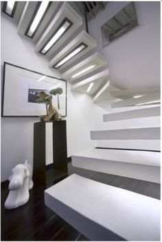 A white floating staircase with lights built into the underside of each tread. Via photographer Veronica Morales Angulo