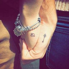 charm bracelet in silver, on a hand with a tiny, heart-shaped padlock tattoo, held by a bigger hand, with a key-shaped t