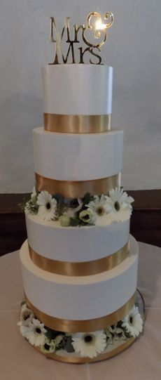 4 Tier buttercream seperator wedding cake, decorated with gold ribbons and an assortment of fresh white flowers. Wedding cake was delivered in Hallam PA.