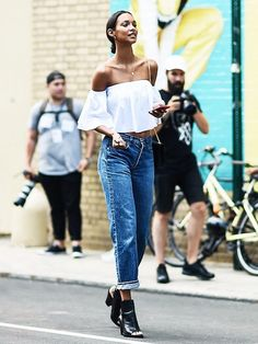 Boyfriend jeans are meant to look as though you stole your boyfriend/fiance/husband's denim from his closet. However, with a ruffled, off-the-shoulder or cropped top, this look can go from boyfriend to your very own, easily. This model wore her boyfriend jeans with black ankle boots and a white, off-shouldered blouse. You can't go wrong with this look.