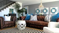 Terrific Ideas for Decorating Home with Tropical Theme : Amazing Living Room Design Feat Beach Theme With Classic Brown Leather Sectional Sofa And Black White Stripe Rug Also Staircase Ideas